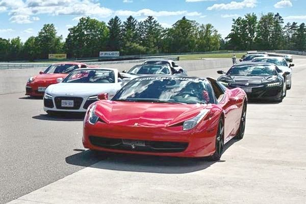 A group of super cars are parked on a race track.