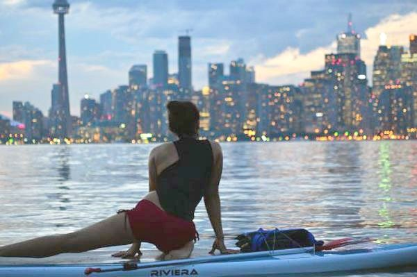 Woman on a paddle board with the Toronto skyline in the background.