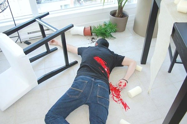 A mock murder scene is shown with a man lying on his stomach with fake blood on his back. A great way to enjoy socially-distanced experiences at home.