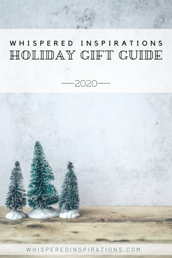 """A stone background and a wooden table top. 3 little snow-covered pine tree figurines are on top of the table. A banner reads, """"Whispered Inspirations, Holiday Gift Guide, 2020"""""""