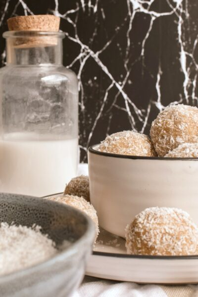 A cutting board with a plate on top that is filled with peanut protein balls. It rests on a napkin with a glass canister of milk with a cork top. Peanuts, a bowl of coconut, and a peanut butter jar.