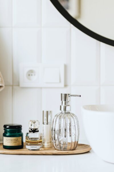 A modern yet rustic bathroom. A white tray with a gold faucet and a tray full with toiletries. Above it is a black round mirror. This article is about ways to spruce up your bathroom.