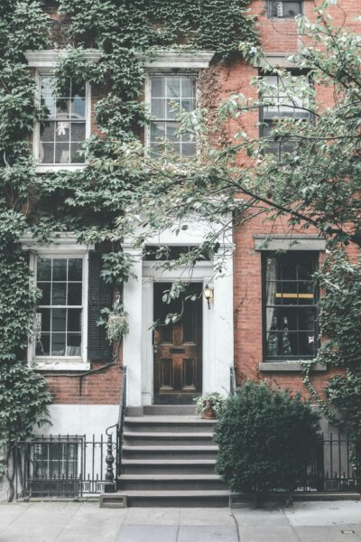 A beautiful home in the city. It has greenery growing all over it. This article is about costs you forget when you buy a new home.