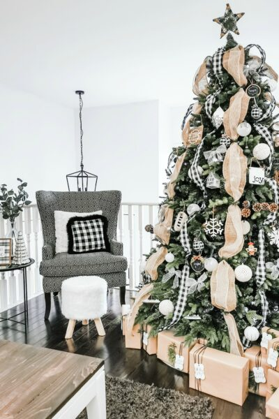 A farmhouse style tree with gifts surrounding it. It is placed in a living room with a wing back chair.