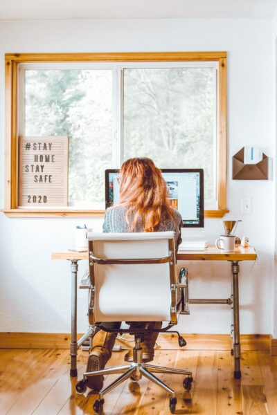 Woman sits at a desk in front of a window. She is working on a computer and her back is facing the camera.