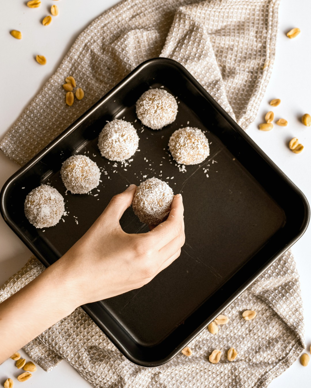 Hand is placing peanut protein balls onto baking sheet.
