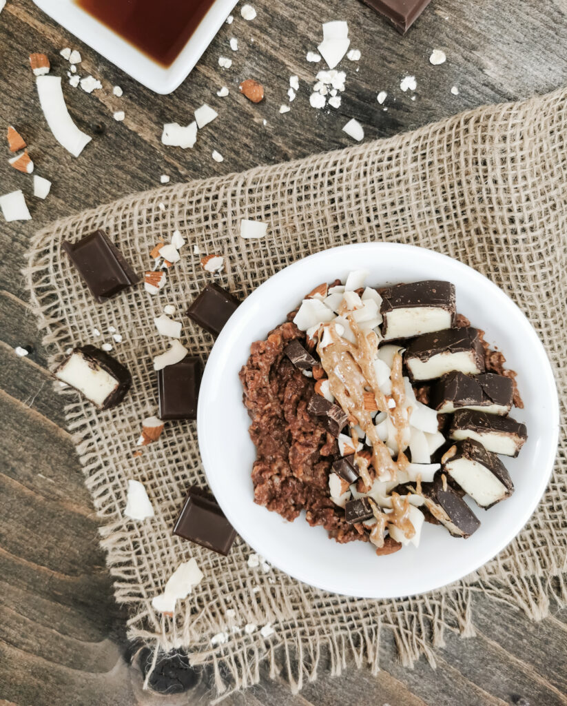 A flat lay of healthy, protein-packed Almond Joy oatmeal. Chocolate, coconut, and almonds surround the bowl.