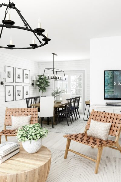 A beautiful farmhouse home. Styled with whites and warm neutrals. A sitting area and dining room are shown with metal chandeliers hang above each area.