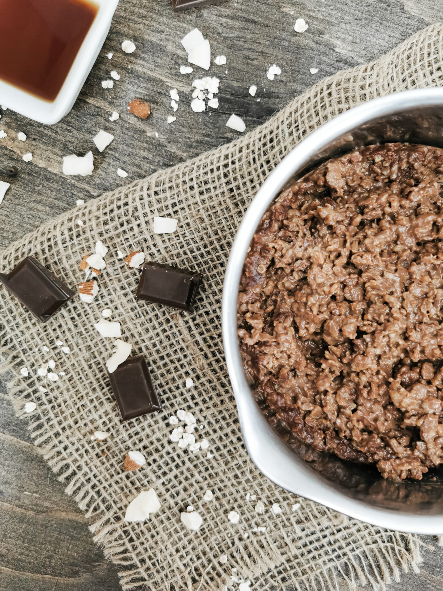 Flatlay of pot with cocoa oatmeal. Maple syrup, chocolate, almonds, and coconut surround it.
