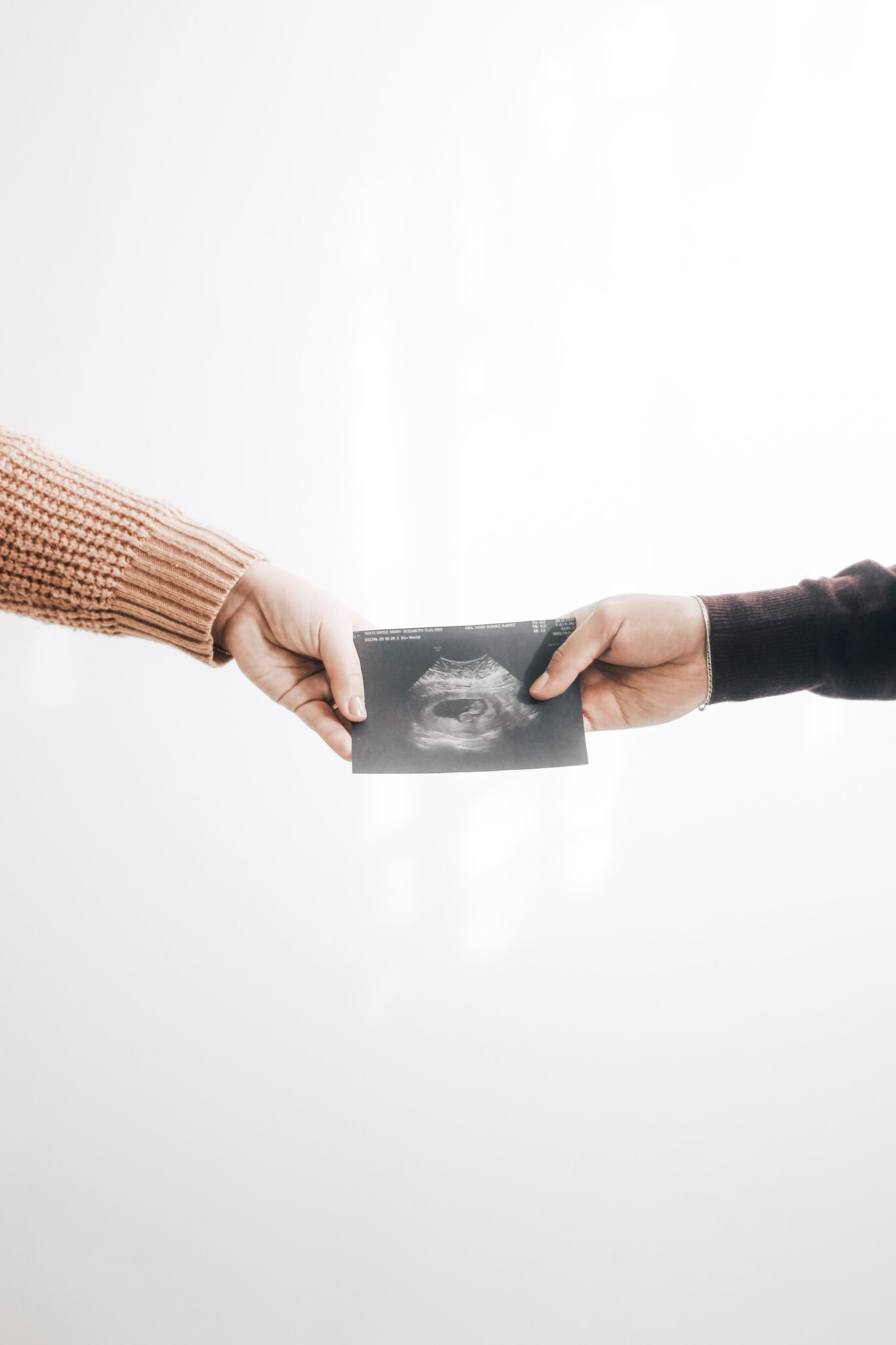 A man and a woman's hand are shown holding an ultrasound.