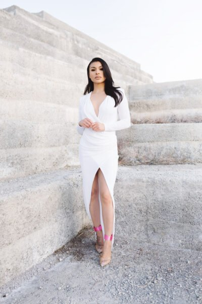 Woman stands in front of a concrete wall wearing a white formal dress. This article explains how to choose a formal dress for your body type.