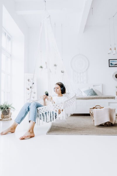 A woman in a bright white room with macramé sits in a macramé swing, listening to something on her phone with headphones.