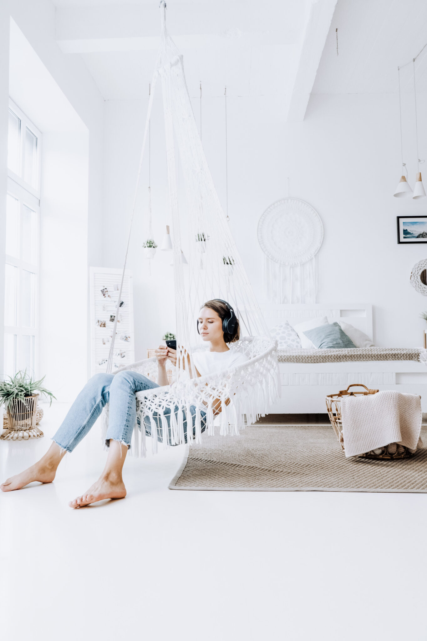 A woman in a bright white room with macramé sits in a macramé swing, listening to something on her phone with headphones. A great place to enjoy Christian audio books.