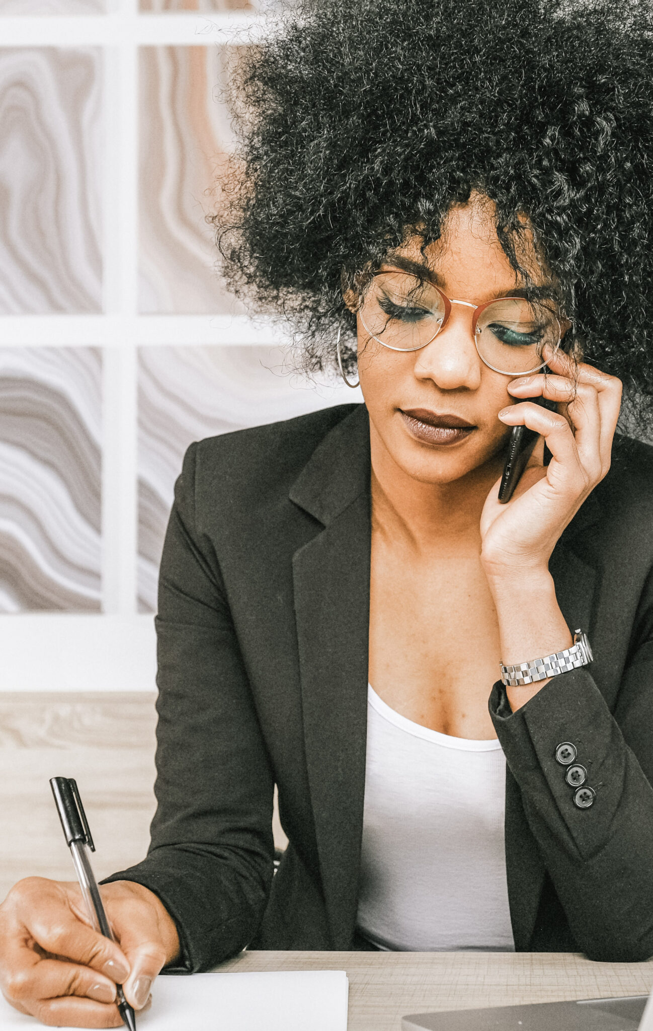 A woman writes down something at her desk on the phone.  These are tips that will help design a functional home office in a small space.