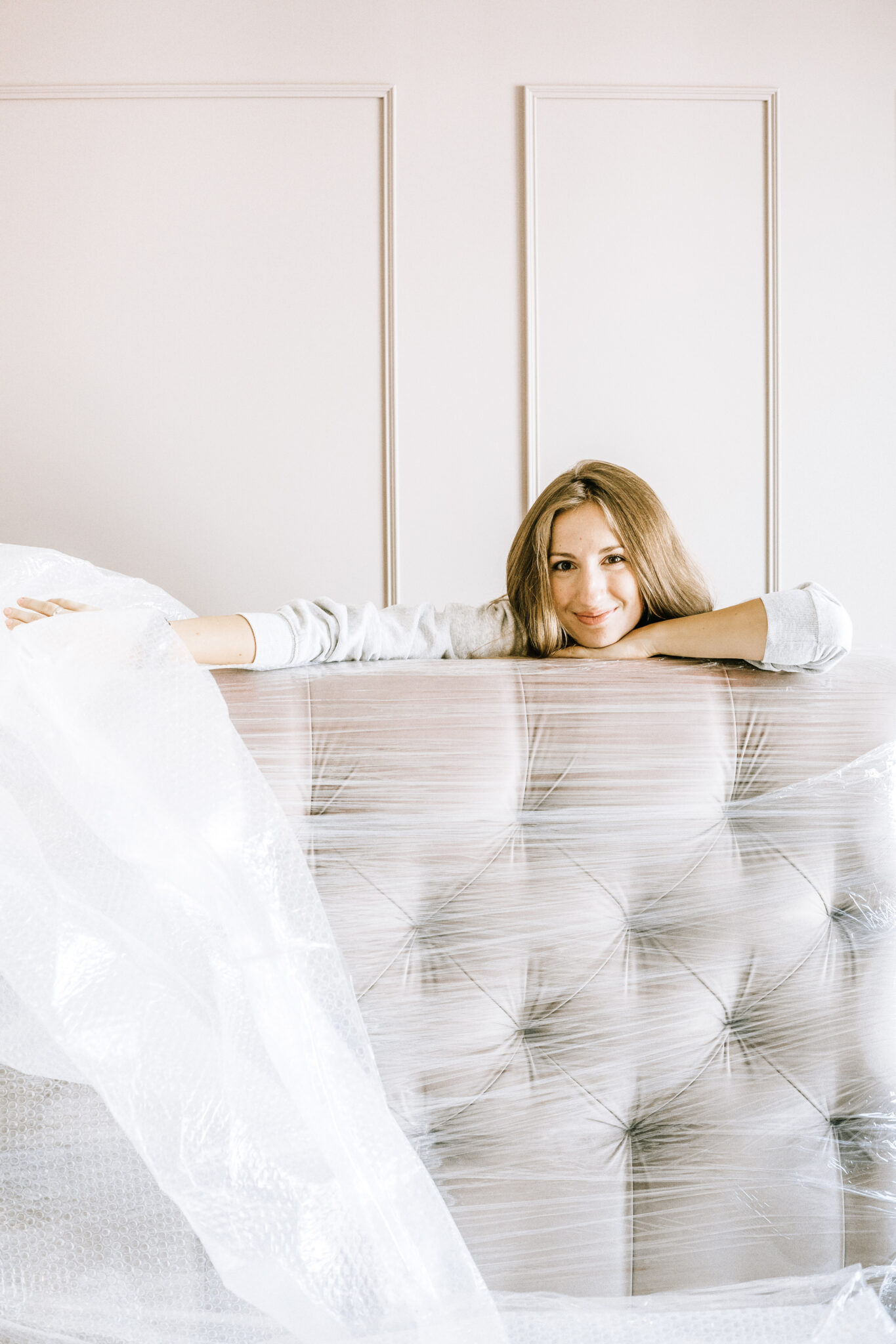 A woman sits behind a couch as she unwraps it while moving in. This article covers how to take the stress out of moving.