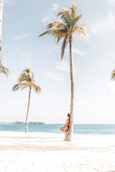 A picturesque beach setting, a woman leans up against a palm tree. The beach is behind her. This article answers how do people afford long-term travel.