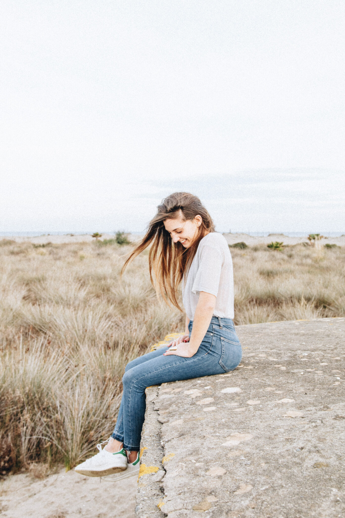 A girls sits on a rock ledge, behind her is wilderneess. She smiles and looks down. She appears to be very confident. This article covers how to revitalize your look and boost your confidence.