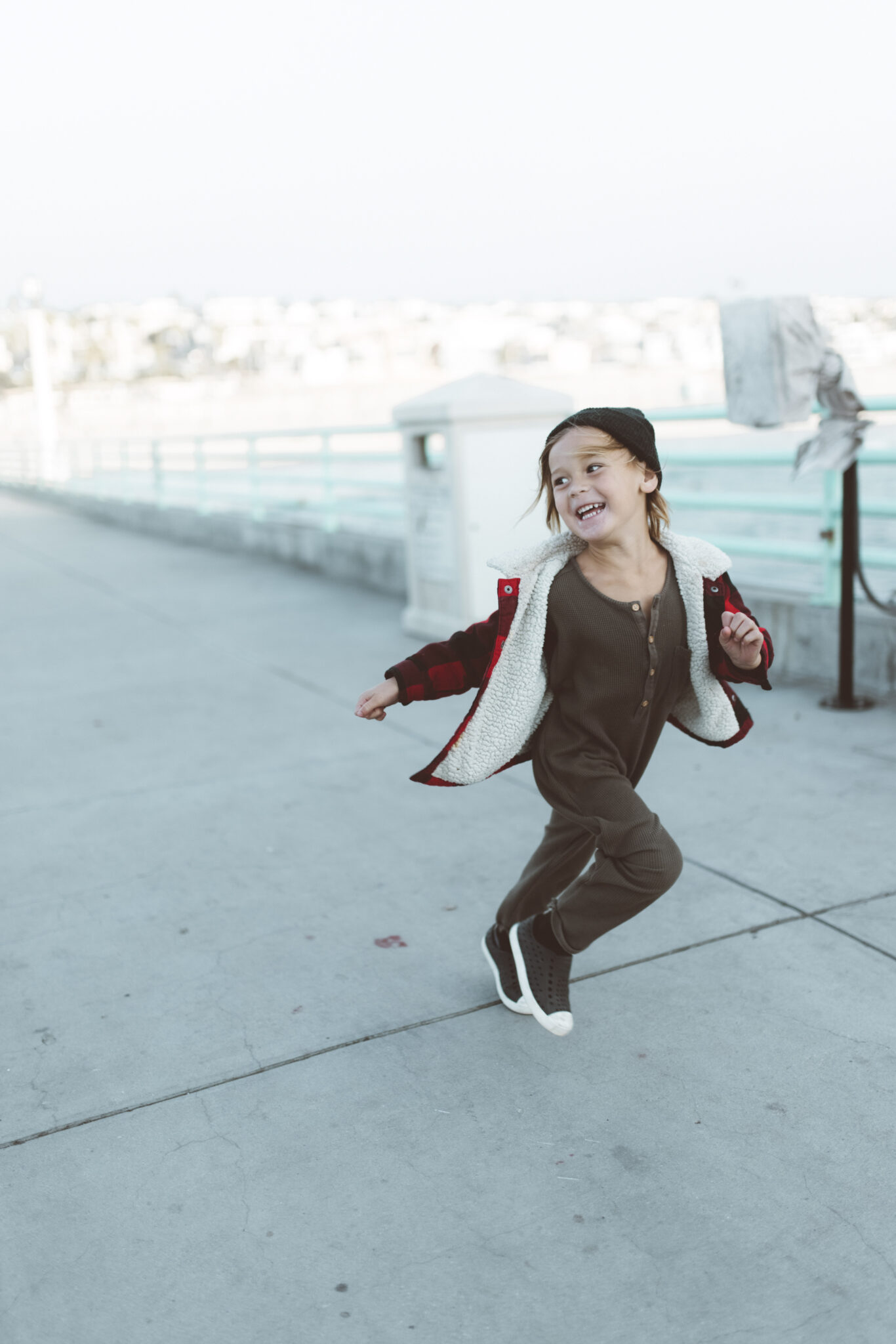 A kid runs happily and freely outside. This article covers  5 ways to teach your kids about money.