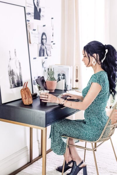 A woman sits in her home office, she wears a green desk and has her hair done. This article gives you tips for the best outfits for working from home.