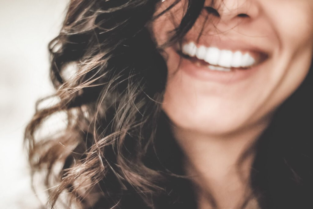 A close up of a woman's face and mouth, she smiles a bright smile. She has dark curly hair. The rest of her face is not seen. This article covers all you need to know about getting a bright smile.