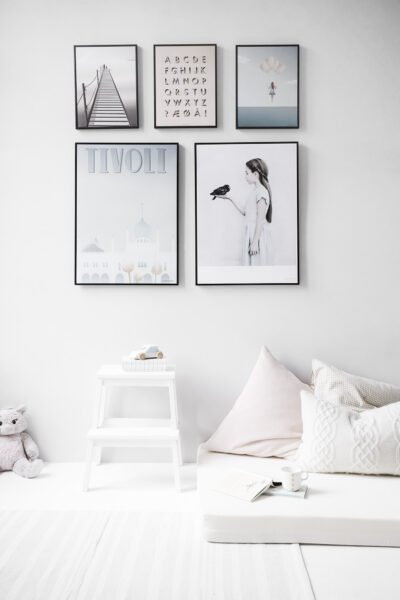 A neutral wall is decorated with several frames with pictures. This article covers how to create the perfect accent wall in your home.