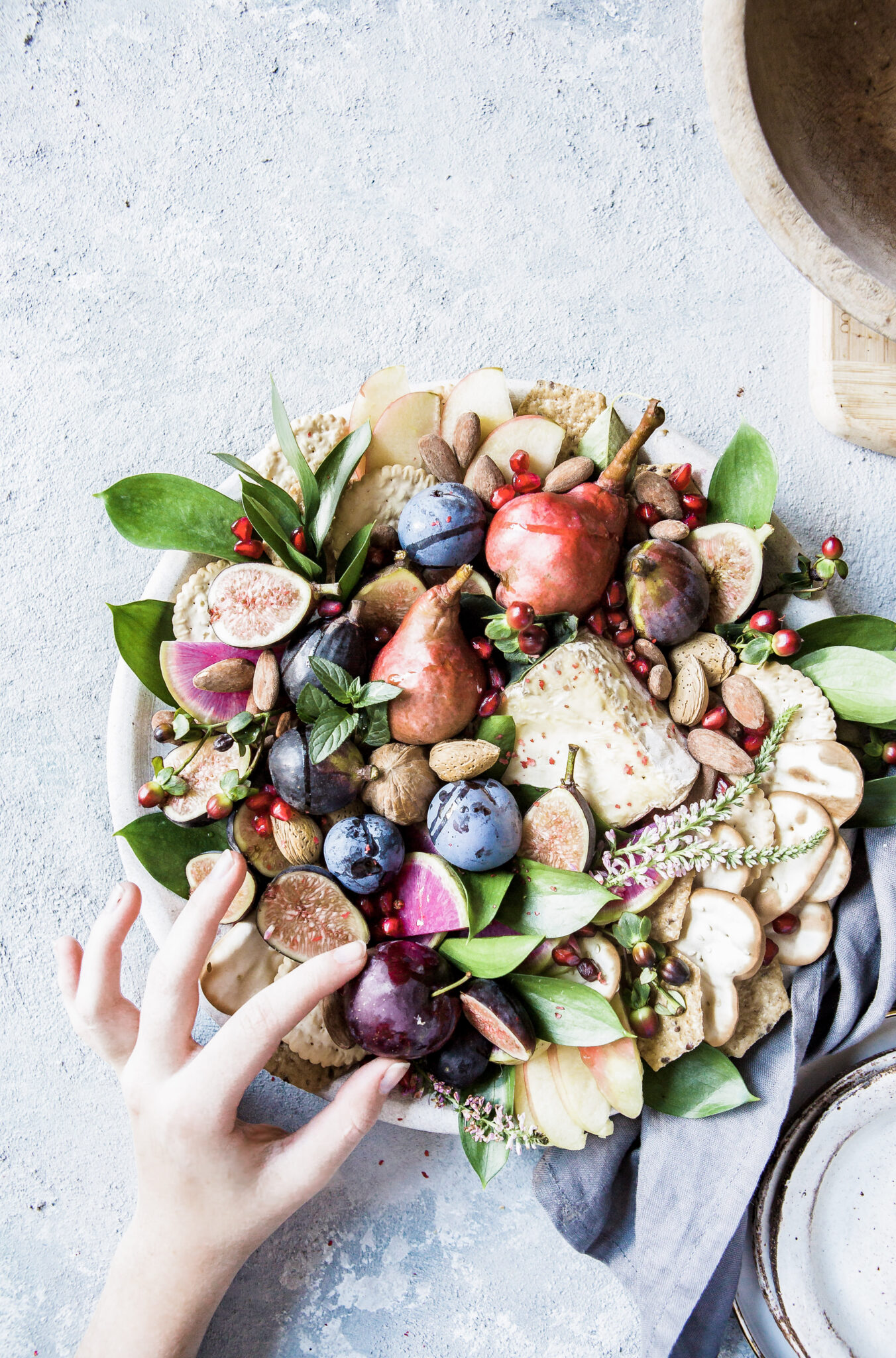 A hand reaches into a bowl stuffed with fresh fruit. This article covers 7 steps to live a healthy lifestyle.