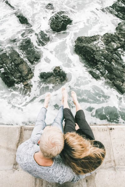 A couple sit together on a ledge and look out to waves crashing below. This article covers 4 things you should take seriously this year.