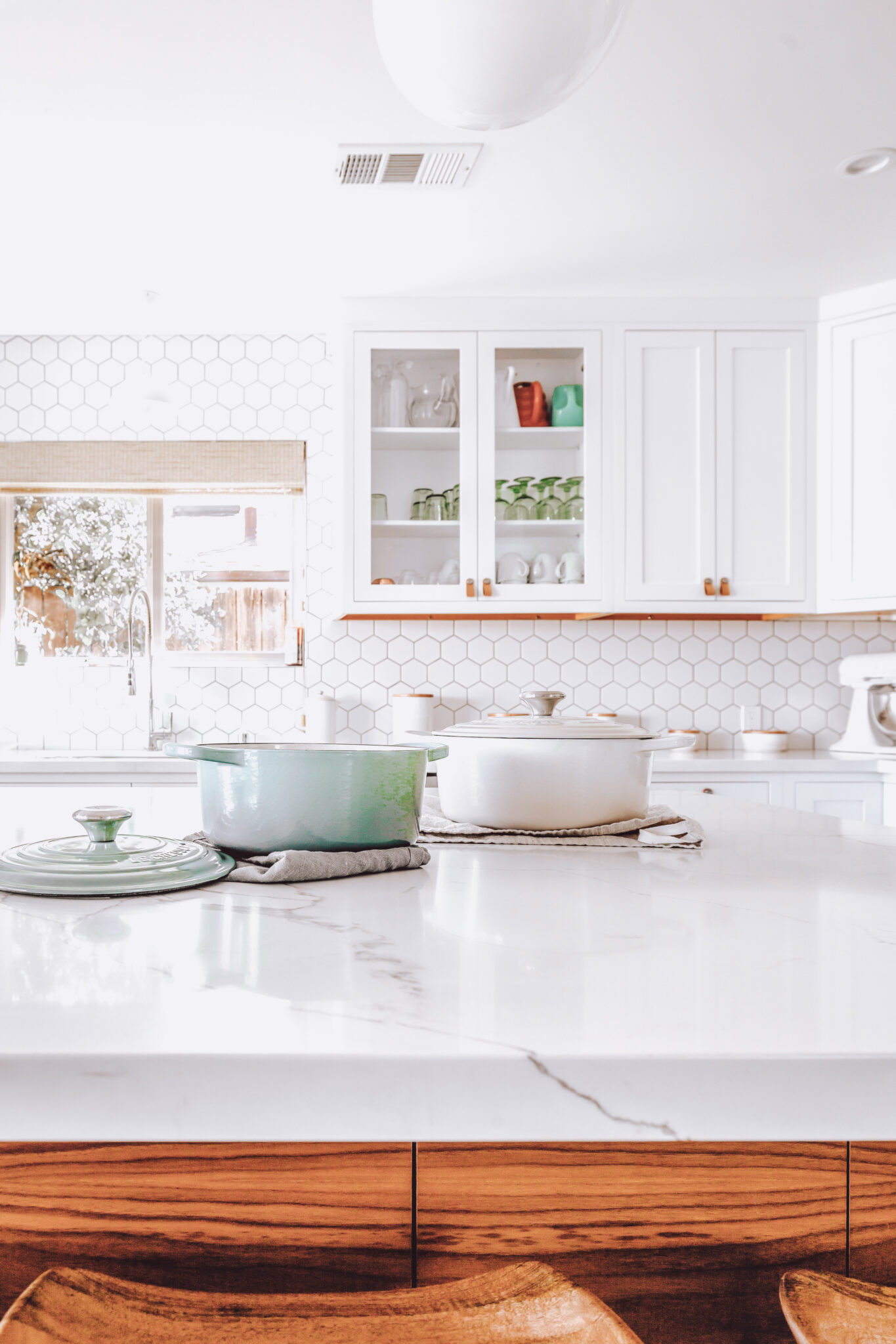 A white and bright kitchen shows a functional kitchen with blinds. This article gives 4 ideas for kitchen blinds.