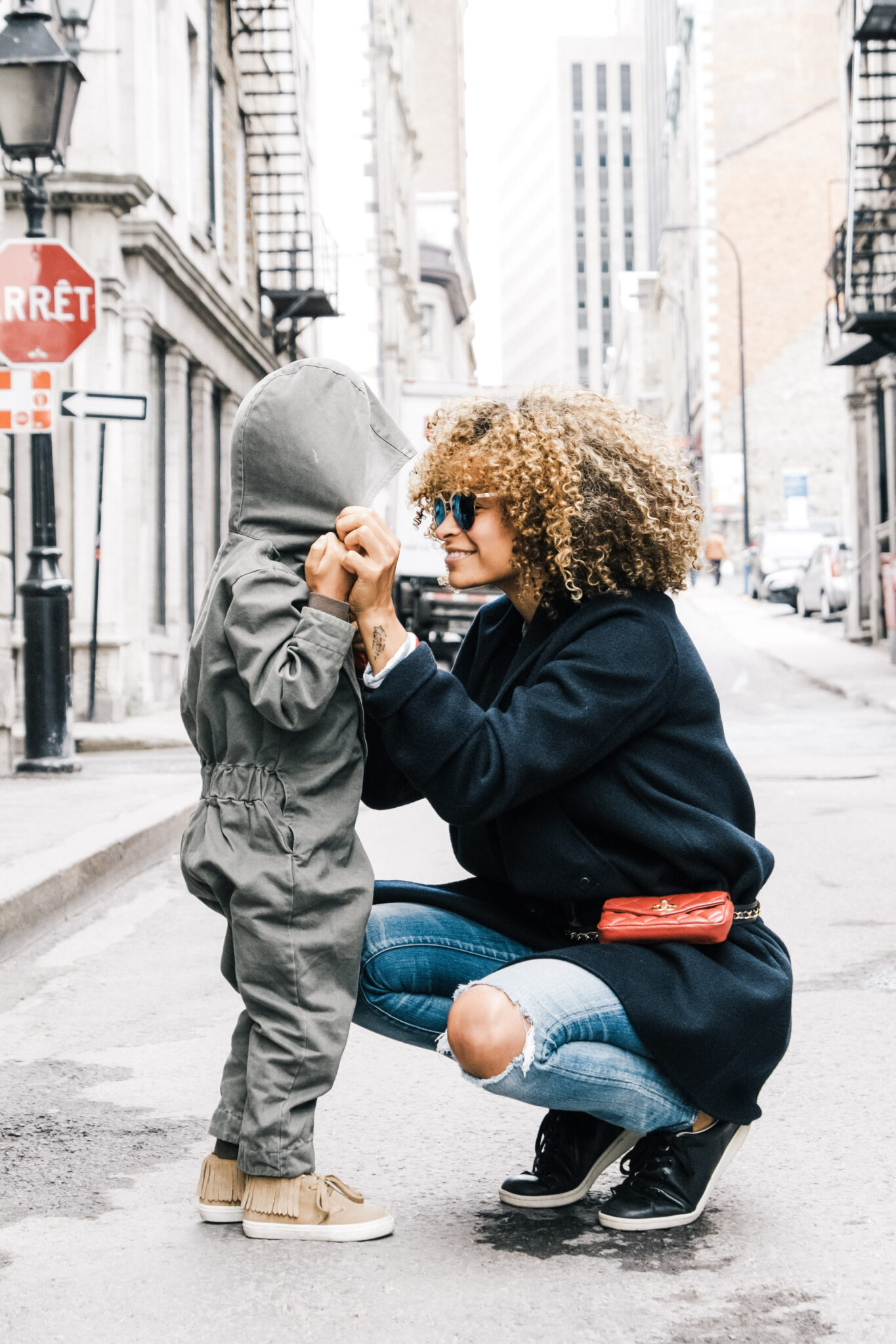 Woman kneels down to the same height as her son and smiles. This article covers 4 vital skills every parent should teach their child.
