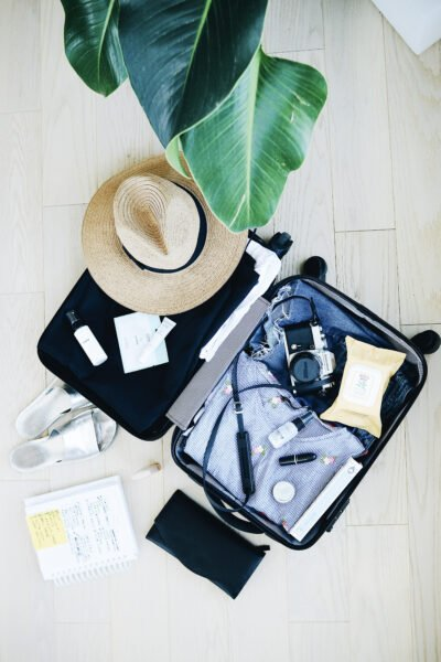 A flat lay shot of an open luggage with clothes, shoes, accessories, and more for a vacation. This articles covers packing tips and tricks for vacation.