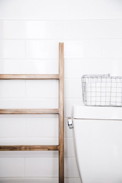 A towel ladder rests next to a toilet. This article covers tips for hiring a plumber.