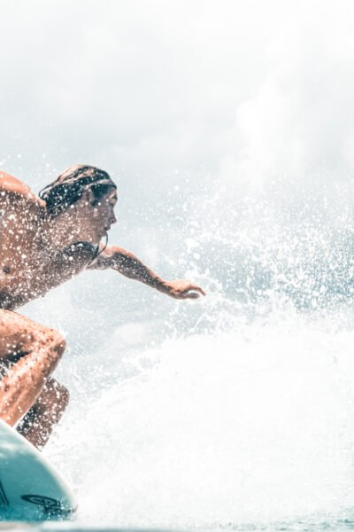Young man surfing and catching a wave. This article covers water activities to enjoy while on vacation.
