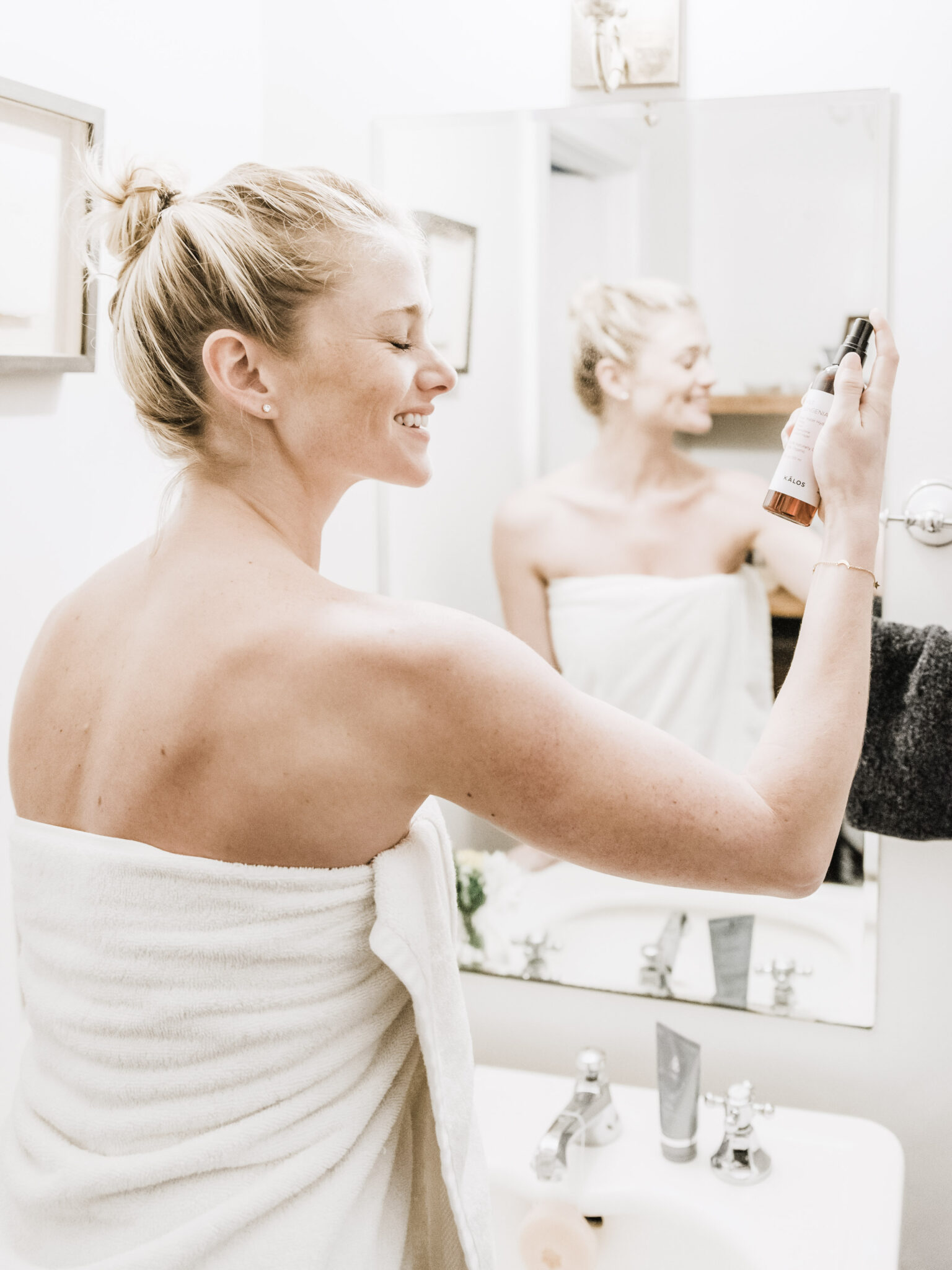 Woman sprays her face with skincare products in the bathroom. This article covers the real cost of beauty in 2021.