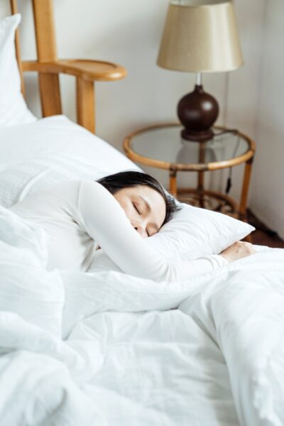 A woman sleeps in a bright room. This article covers 7 bedroom essentials for optimal sleep.