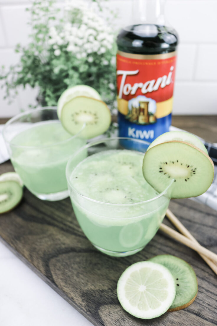 A top view of two cocktails on a board, they're surrounded my kiwi and lime slices and Torani Kiwi Syrup.
