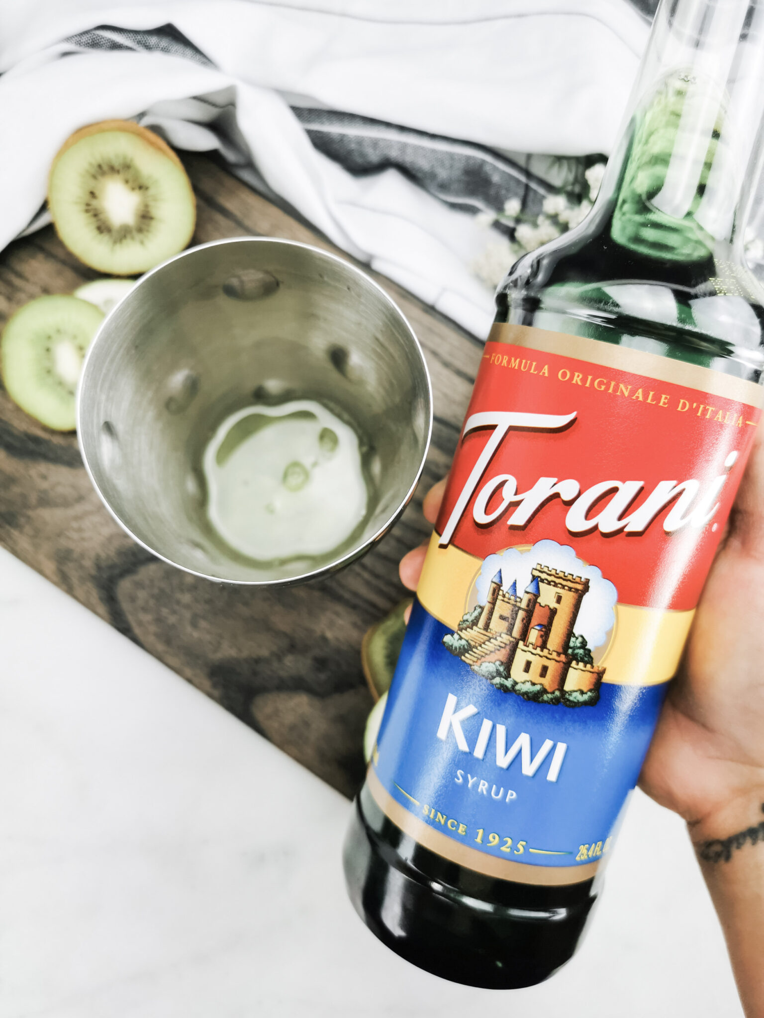 Holding the Torani Kiwi syrup before pouring it into the cocktail shaker.