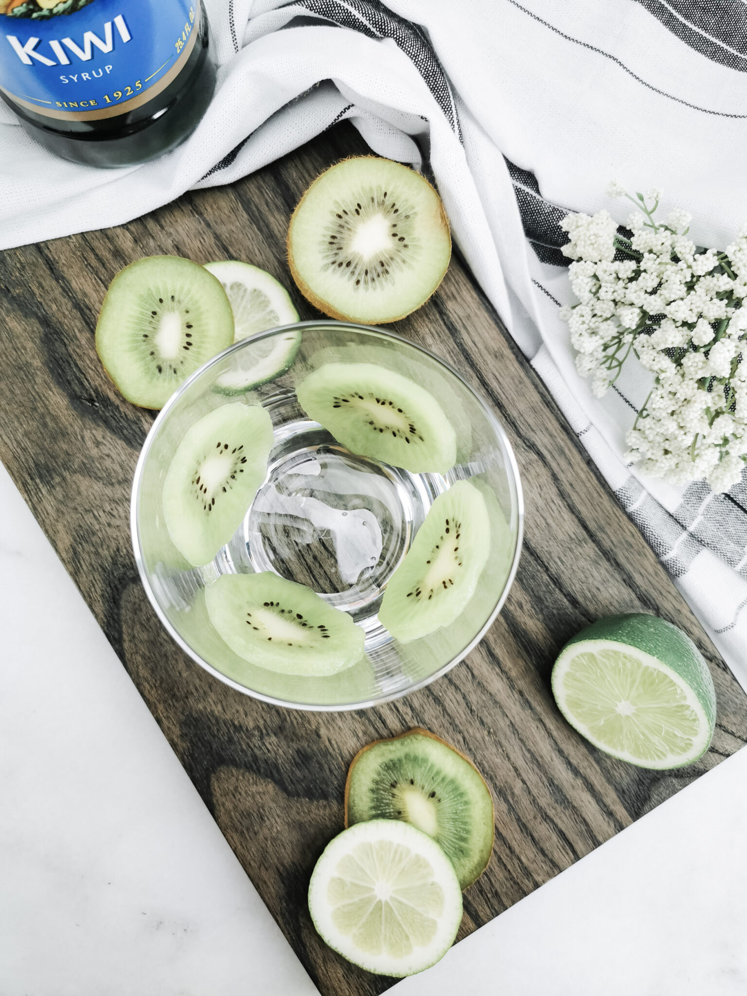 Overhead view of double old-fashioned cups lined with thin-sliced kiwis, ready for a the finished cocktail.