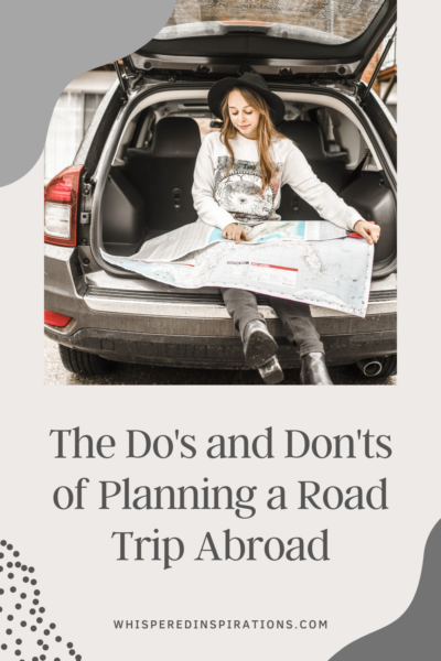 A girl sits in the back of her car holding and reading a map for a road trip. This article covers the do's and don'ts of planning a road trip abroad.