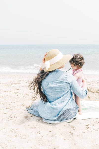 Mother sitting on the beach with her child. This article covers tips for a safe and fun family trip.