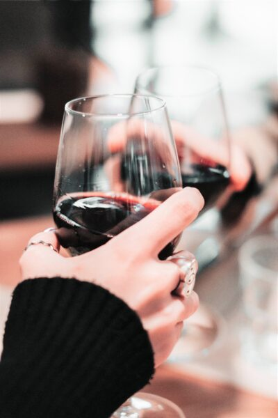 Two women hold a glass of wine and toast. This article covers the brand of Cameron Diaz meets Avaline the organic wine.