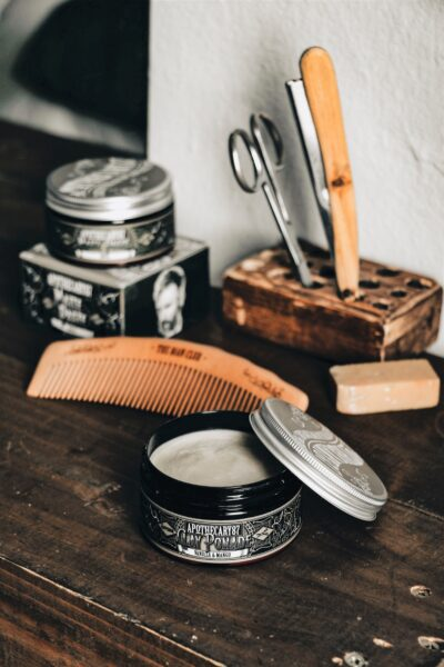 Tools of a barber are shown on a wooden table. Thera are scissors, pomade, brushes, and more. This article covers useful tips for choosing a barber.