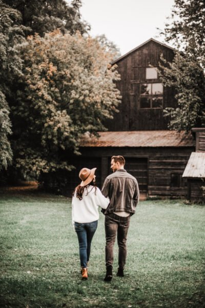 A couple walking towards their rural farmhouse. This article covers how to maximize the benefits of rural living.
