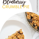 A blueberry crumble pie with a piece missing. The piece of pie is on a white plate on top of a napkin. There is a small bowl of blueberries shown. This article covers a Blueberry Crumble Pie recipe.