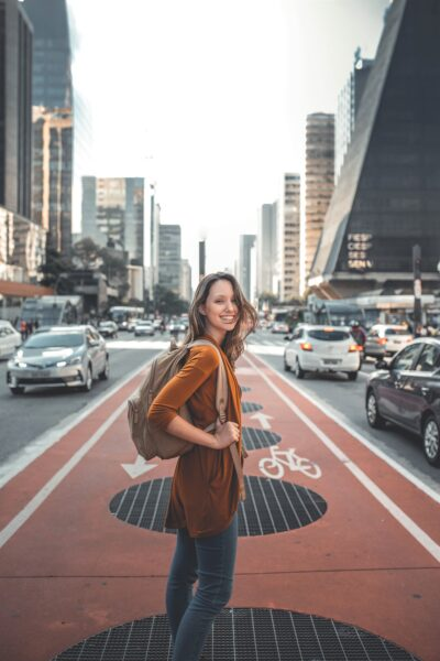 A woman is backpacking through Sao Paolo and takes a picture in the city streets. This article covers how much time is enough for traveling?