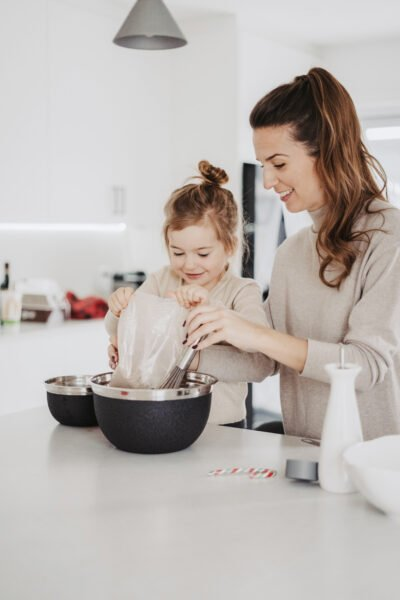 A mother and daughter are in the kitchen baking. They are smiling and happy. This article covers lists 5 steps for more effective parenting.