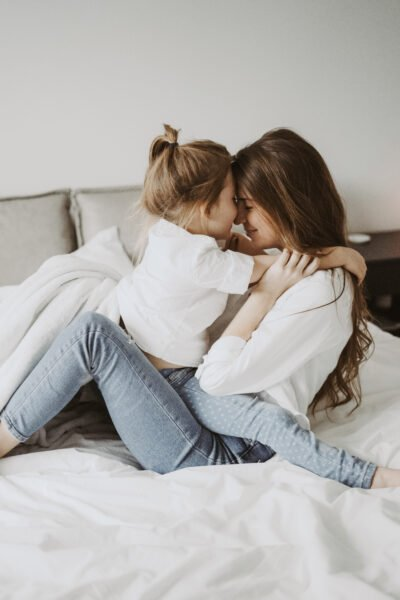 A mom and her daughter cuddle nose-to-nose on the bed. They are smiling and very happy. This article covers parenting hacks that make a world of a difference.