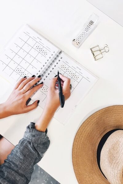 Woman writes in her agenda and planner. Organizing her schedule. This article covers three things you should remember as a working mom.