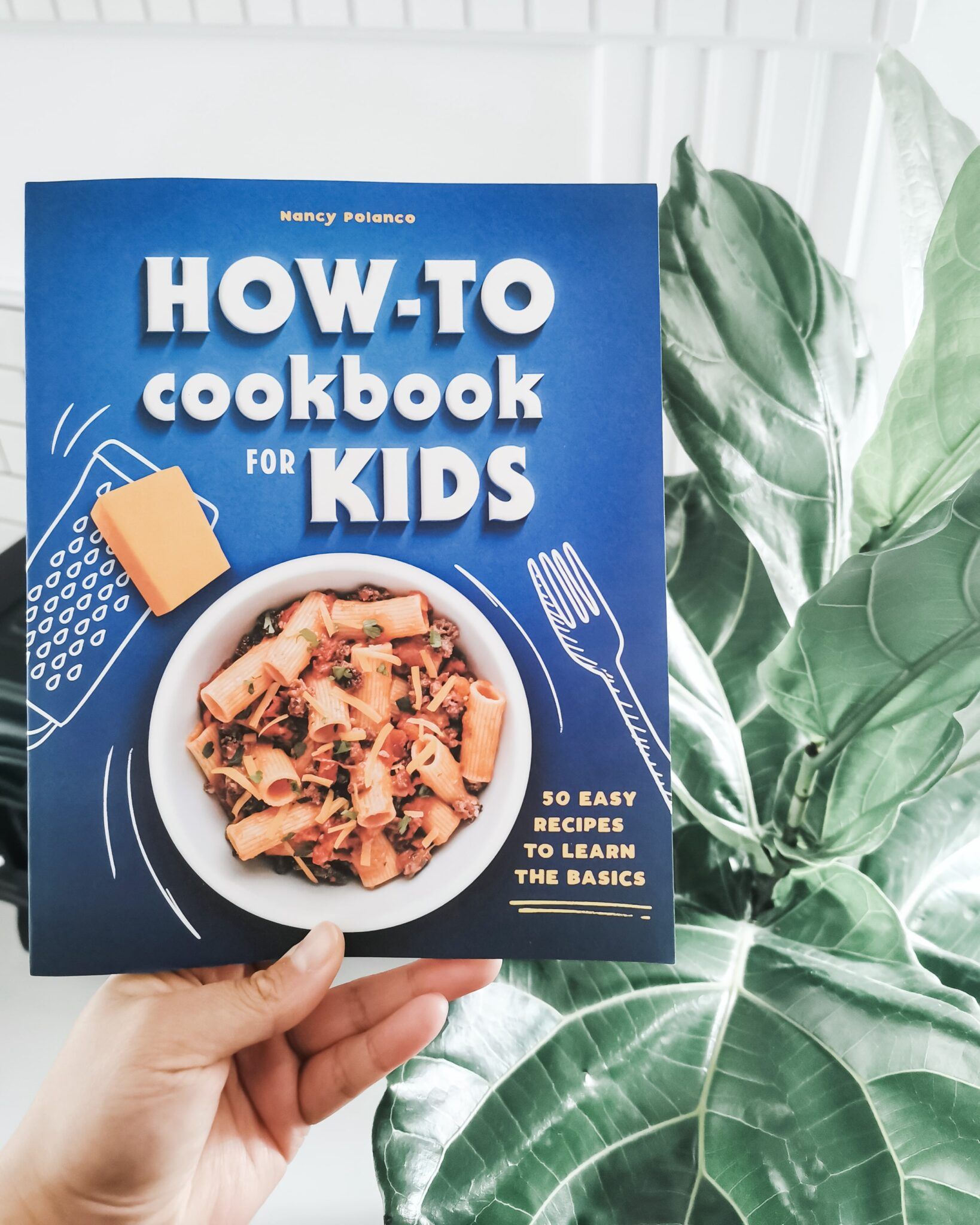 The new cookbook, How-To Cookbook for Kids is being held up against a fiddle leaf plant and a white fireplace.