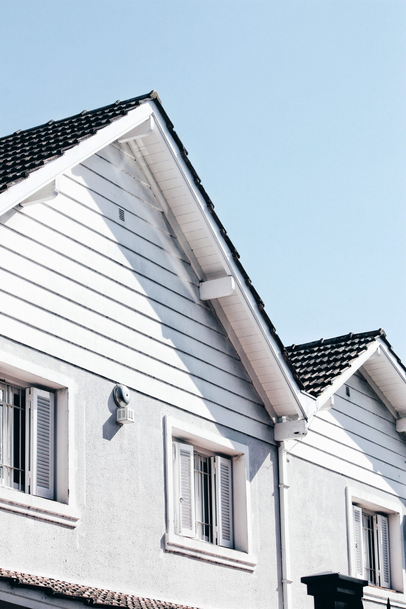 A close up of two roofs of townhouses are shown against a blue sky. This article covers tips to get your home sale ready.