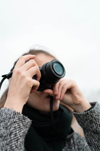 A woman holds a DSLR to her eye and shooting something. She is wearing a black and jacket. This article covers a guide to documenting any trip.